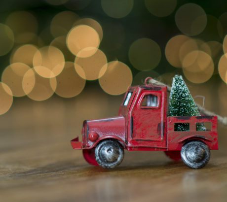 Cute vintage toy red truck decoration with a Christmas tree in the back in front of blurry lights from the Christmas tree.