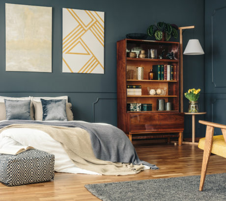 Antique wooden furniture in a stylish dark gray bedroom interior with emerald green and golden decorations and wainscoting